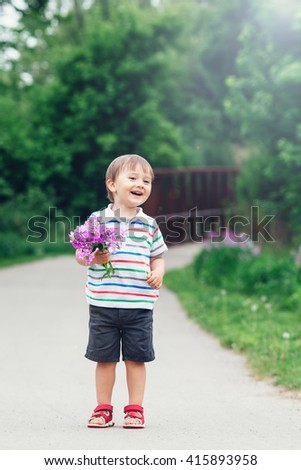 Portrait of a cute adorable funny little smiling boy toddler walking in park with lilac purple pink flowers in hands on bright summer day, lens flare from above, mothers day - stock photo