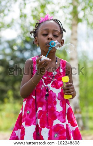 Portrait of a cute african american little girl blowing soap bubbles - stock photo