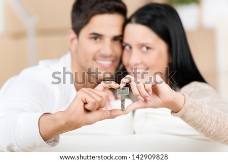 Portrait of a cute and happy young couple holding their new house key inside a heart sign. - stock photo