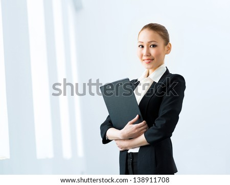 Portrait of a cute asian business woman stands with his arms crossed - stock photo