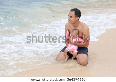 portrait of a cute baby enjoying summer on a beach with her father - stock photo