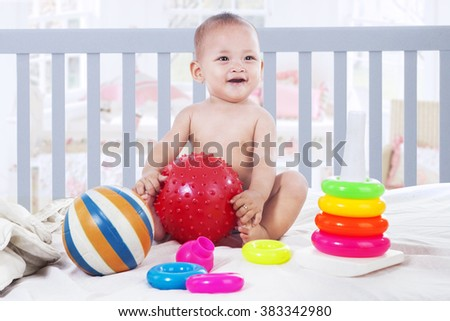 Portrait of a cute baby girl sitting on the baby crib while playing with toys