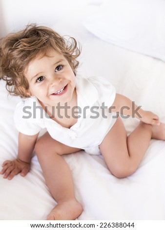 Portrait of a cute baby girl smiling from above. The pretty happy toddler is on a bed