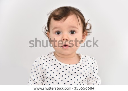 Portrait of a cute baby girl with beautiful big brown eyes. Isolated on a light gray background.  - stock photo