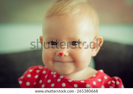 Portrait of a cute baby in red dotted dress - stock photo