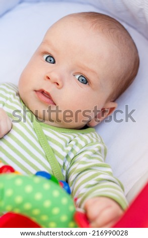 portrait of a cute baby lying in pram with toy