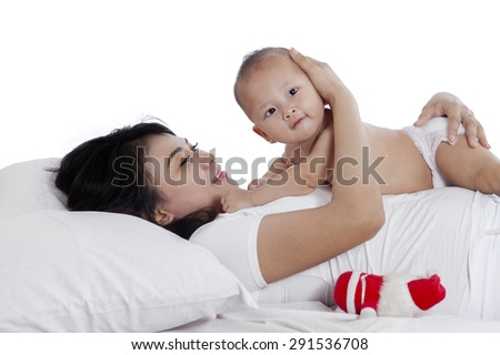 Portrait of a cute baby lying over her mother tummy while looking at the camera