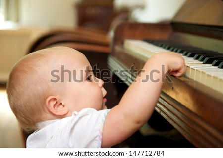 Portrait of a cute baby playing on piano - stock photo