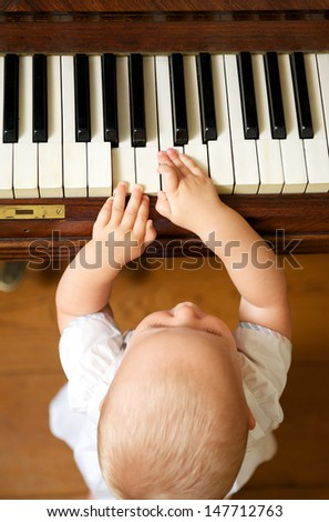 Portrait of a cute baby playing piano - from above