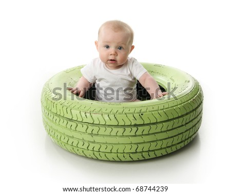 Portrait of a cute baby sitting inside a green painted tire, isolated on white - stock photo