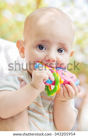 portrait of a cute baby sucks rattle outdoors - stock photo