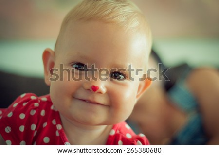 Portrait of a cute baby with heart nose - stock photo