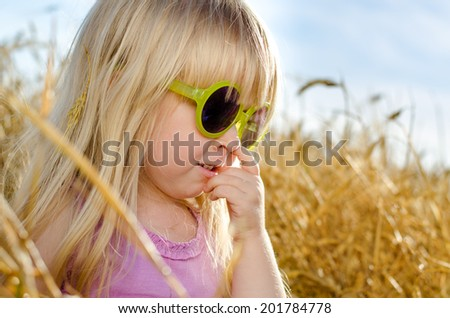 Portrait of a cute blond little girl wearing plastic sunglasses while looking up from the middle of a ripe yellow wheat field, in a warm sunny day in the countryside - stock photo