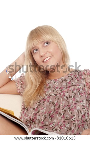 portrait of a cute blonde reading a magazine - stock photo