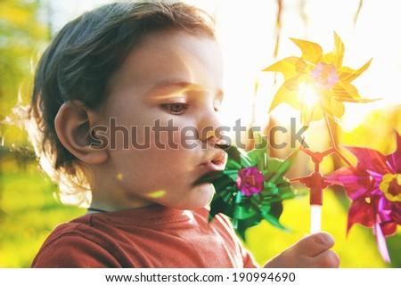 Portrait of a cute boy blowing wind wheel in sunshine - stock photo