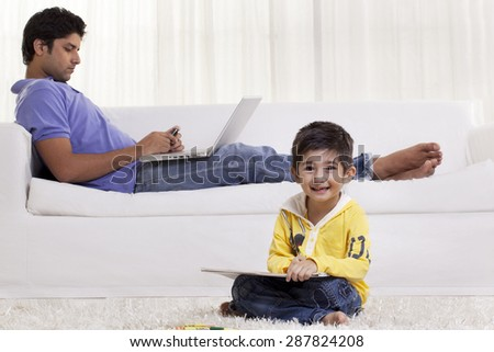 Portrait of a cute boy drawing while father texting in the background - stock photo