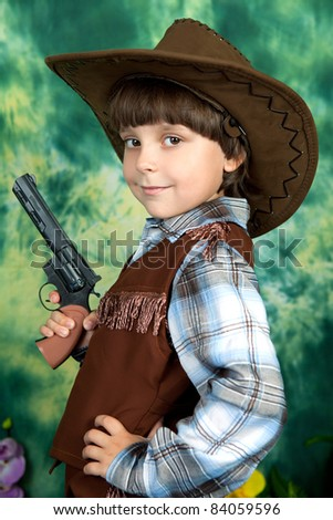 Portrait of a cute boy in a cowboy suit with a pistol on a green background
