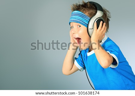 Portrait of a cute boy listening to music on headphones over grey background. - stock photo