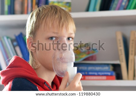 portrait of a cute boy makes inhalation home