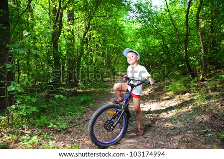 Portrait of a cute boy on bicycle in forest path - stock photo