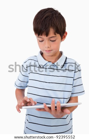 Portrait of a cute boy using a tablet computer against a white background - stock photo