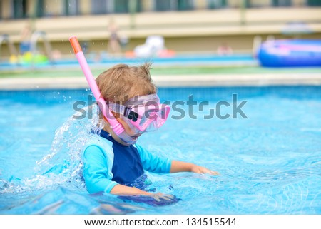 Portrait of a cute boy wearing a mask for diving in swimming pool - stock photo