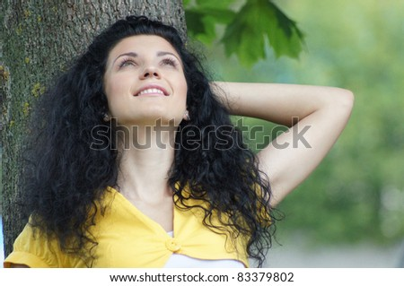 portrait of a cute brunette posing in the park - stock photo