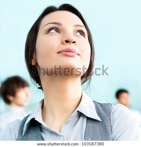 Portrait of a cute business woman with colleagues at the background. Indoors at modern office building center - stock photo