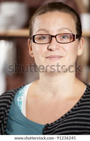 Portrait of a cute, casual woman looking into camera smiling. - stock photo