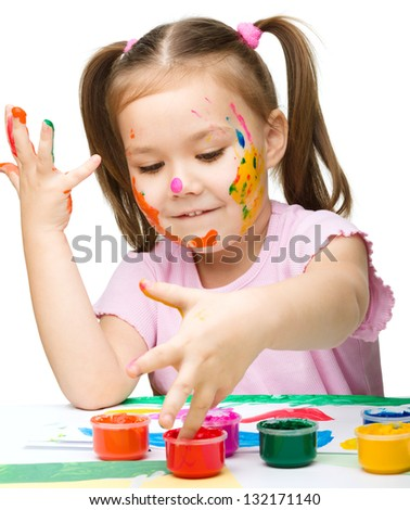 Portrait of a cute cheerful girl playing with paints, isolated over white - stock photo