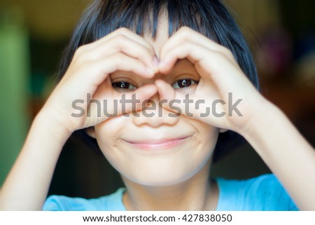 Portrait of a cute cheerful girl showing her hands and smiling, blurred background - stock photo
