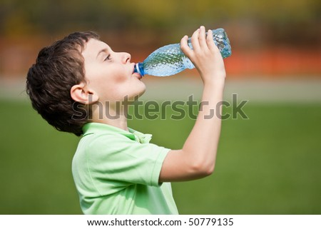 Portrait of a cute child drinking water from a bottle outdoor - stock photo
