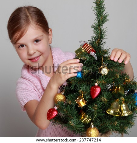 Portrait of a cute child in a knitted dress decorates a Christmas tree on a gray background on Holiday/Smiling girl near a Christmas tree - stock photo