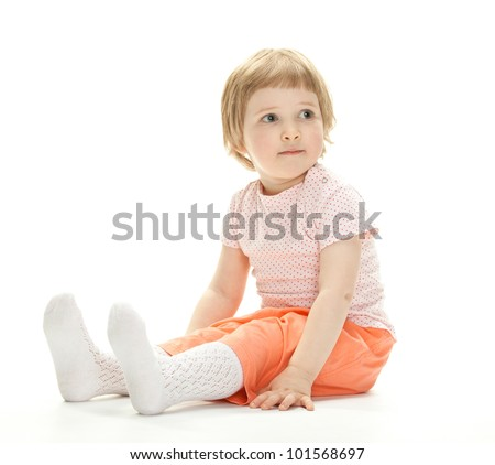 Portrait of a cute child sitting on the floor; studio shot on white background