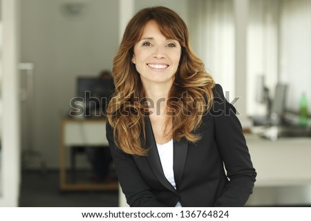 Portrait of a cute confident business woman in office - stock photo