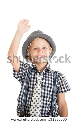 Portrait of a cute curly blond European boy wearing a plaid shirt, tie and hat. The boy waved his hand. Studio shot, isolated on white background. - stock photo
