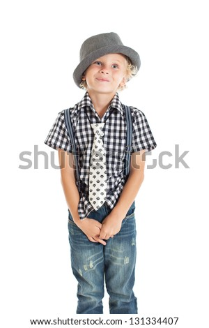 Portrait of a cute curly blond European boy wearing a plaid shirt, tie, suspenders and hat. Studio shot, isolated on white background.