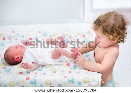 Portrait of a cute curly toddler girl playing with the feet of her newborn baby brother on a changing table - stock photo