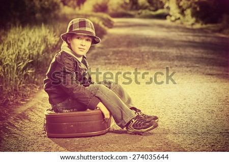 Portrait of a cute dreamy boy sitting on the old suitcase outdoor. Summer day. Adventure. - stock photo