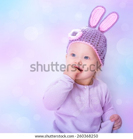 Portrait of a cute Easter bunny baby girl over blur pink blue bokeh background, sweet little child wearing purple hat with rabbit ears, celebrating religious holiday - stock photo
