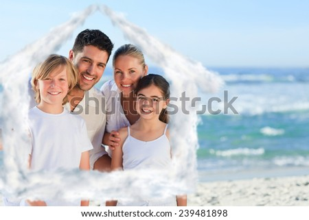 Portrait of a cute family at the beach against house outline in clouds