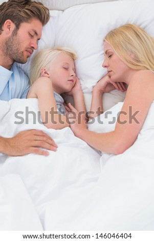 Portrait of a cute family sleeping in bed