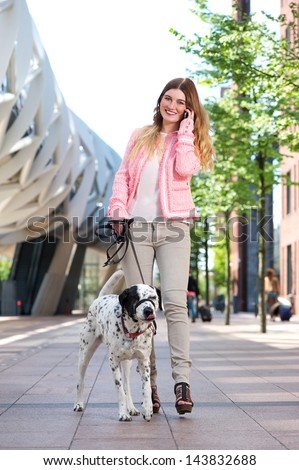 Portrait of a cute female walking her dog outdoors and talking on mobile phone - stock photo