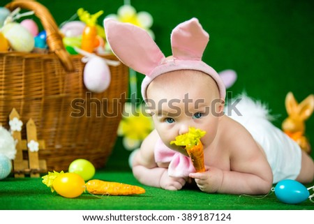 Portrait of a cute funny baby dressed in Easter bunny ears with eggs - stock photo