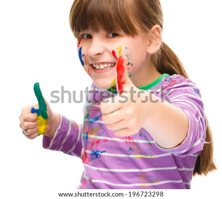 Portrait of a cute girl playing with paints and showing thumb up sign using both hands, isolated over white - stock photo