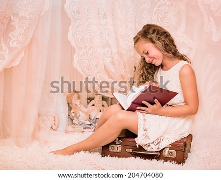 Portrait of a cute girl reading book