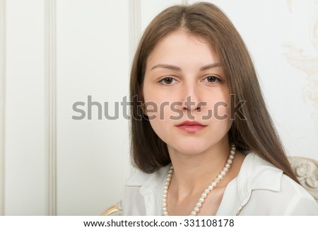 Portrait of a cute girl with beautiful long straight hair in a white blouse on a light background