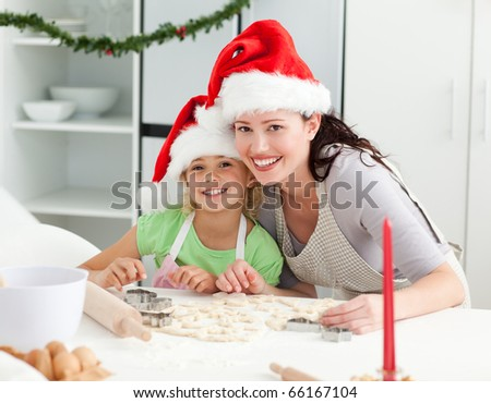 Portrait of a cute girl with her mother baking Christmas cookies in the kitchen