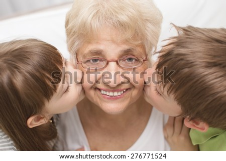 portrait of a cute grandchildren kissing grandmother - stock photo
