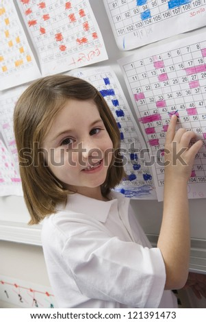 Portrait of a cute happy girl pointing a date on calendar in the classroom